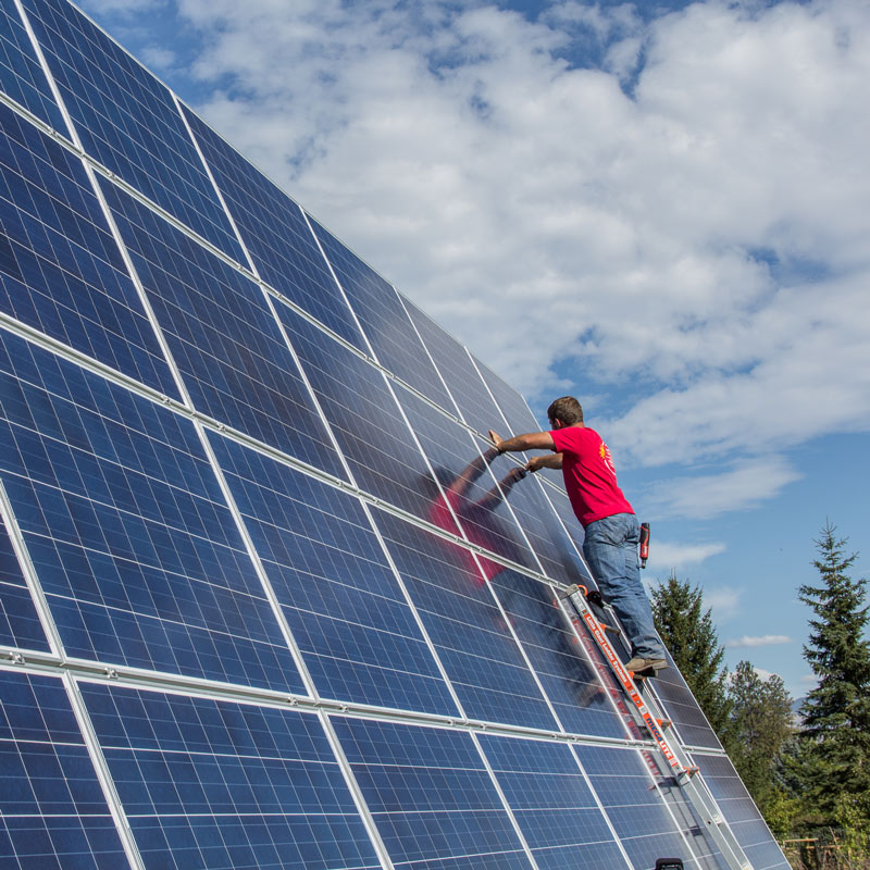travis jordan working on large solar energy array hamilton montana